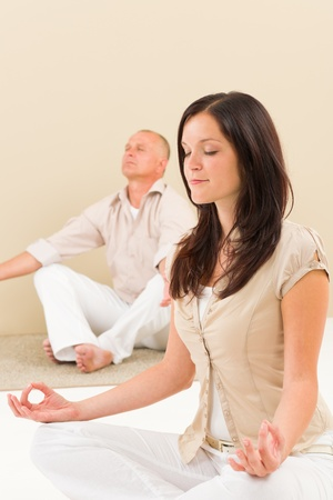 Casual business yoga young woman meditating with senior businessman colleague photo