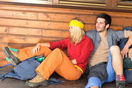 tramping: Tramping young couple backpack relax sitting by wooden cottage