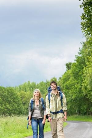 tramping: Paseos mochila pareja joven caminando sobre la carretera de asfalto rural Foto de archivo