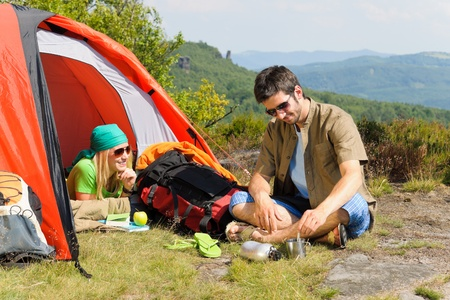 Happy camping couple with tent backpack in sunny countryside photo