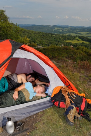 Camping young couple backpackers sleeping in tent with climbing gear photo
