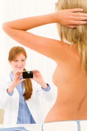 Plastic surgery female doctor take picture of woman patient breast Stock Photo - 10135035