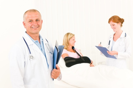 Two medical doctors professional with hospital patient lying in bed Stock Photo - 10180232