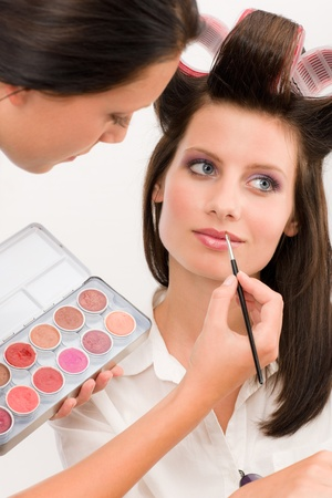 Make-up artist woman fashion model apply lipstick from color palette photo