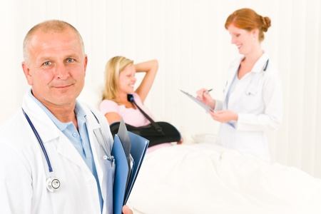 Two medical doctors professional with hospital patient lying in bed photo