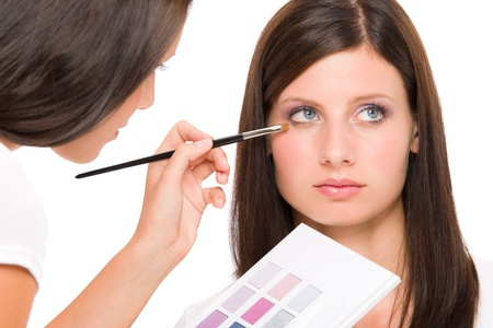 Make-up artist woman fashion model apply eyeshadow from color palette photo