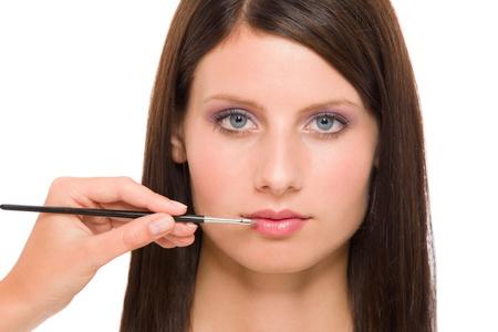 Professional makeup model portrait artist apply glossy lipstick using brush photo