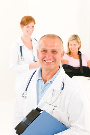 Two medical doctors professional with hospital patient lying in bed Stock Photo - 10223143