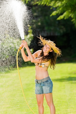 water hose: Summer garden grass woman play with water hose sunny day Stock Photo