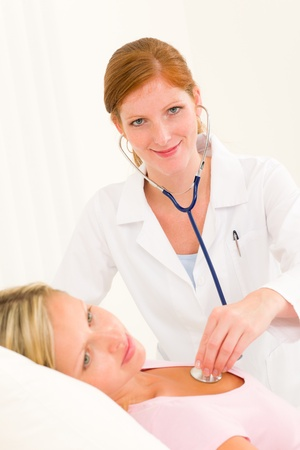 Medical professional doctor stethoscope examine woman patient lying in bed Stock Photo - 10223139