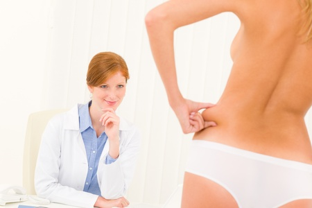 consultation woman: Plastic surgery consultation female doctor patient pinch skin on hips