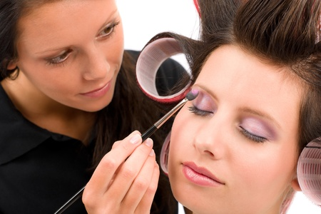 Make-up artist woman fashion model apply eyeshadow with brush photo