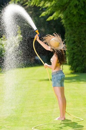 mangera: Mujer de verano jardín césped jugar con día soleado de la manguera de agua