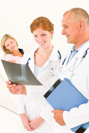 Medical doctors look at x-ray hospital patient in bed broken arm Stock Photo - 10248336