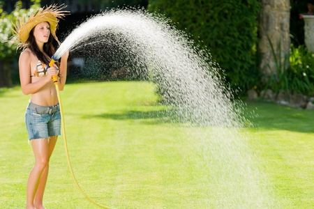Summer garden grass woman play with water hose sunny day photo