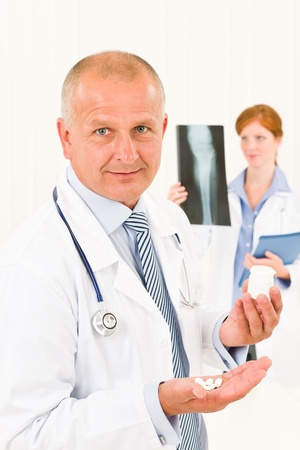 Medical doctor team senior male holding pills young female colleague photo
