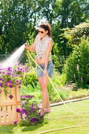 hose: Summer garden smiling woman watering hose flower sunny day Stock Photo