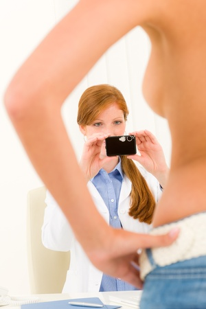 Plastic surgery female doctor take picture of woman patient breast Stock Photo - 10259805