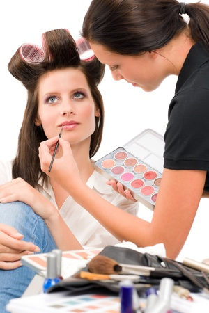 Make-up artist woman fashion model apply lipstick from color palette