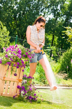 Summer garden smiling woman watering hose flower sunny day photo