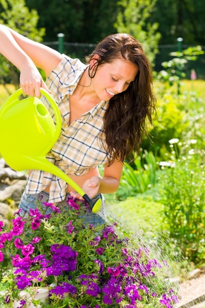 Gardening smiling woman watering violet flowers with can photo