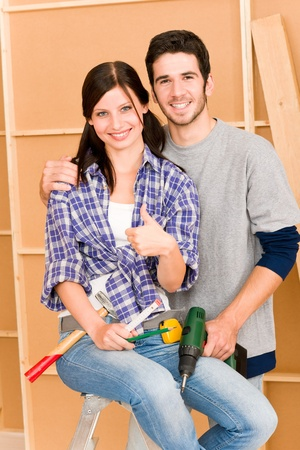 DIY home improvement young happy couple with hand drill ruler Stock Photo - 10397148