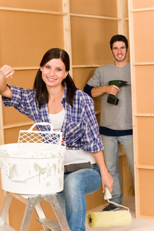 Home improvement: young happy couple fixing new house renovating wall photo