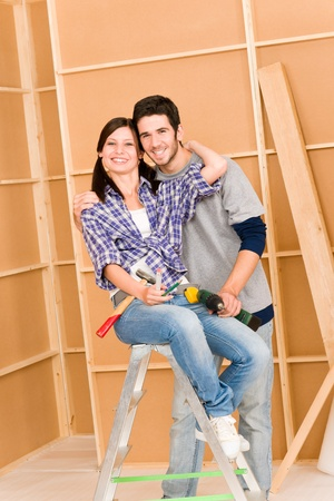 Home improvement young happy couple with repair tool hand drill ruler photo