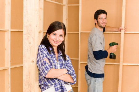 Home improvement smiling young couple fixing wall with hand drill photo