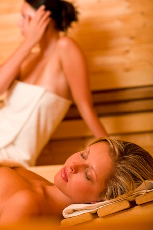 sauna: Sauna two healthy beautiful women relaxing sweating lying covered towels Stock Photo