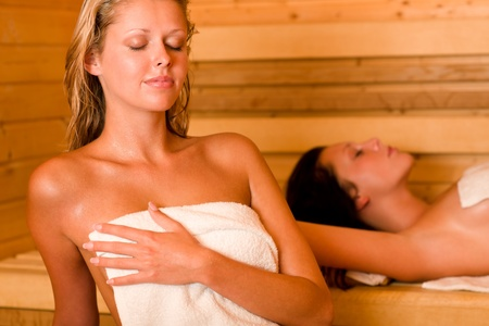 perspiration: Sauna two healthy beautiful women relaxing sweating lying covered towels Stock Photo