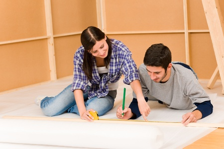 Home improvement young couple working on floor renovations photo