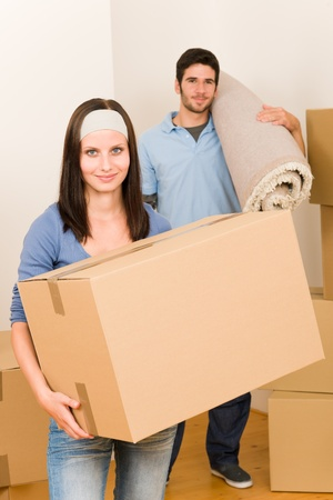 Happy couple with boxes and carpet moving into new home photo