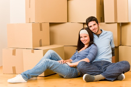 cardboard house: Moving into new home young happy couple sitting on floor