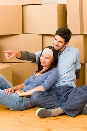 Moving into new home young happy couple sitting on floor photo