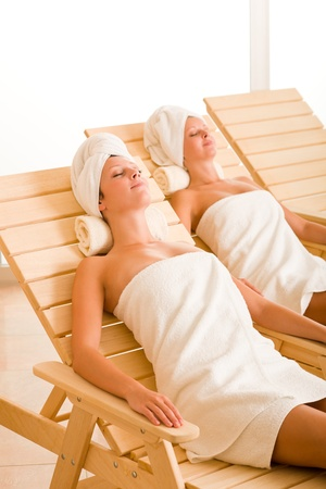wrapped in a towel: Spa luxury relax room two beautiful women lying on sun-beds