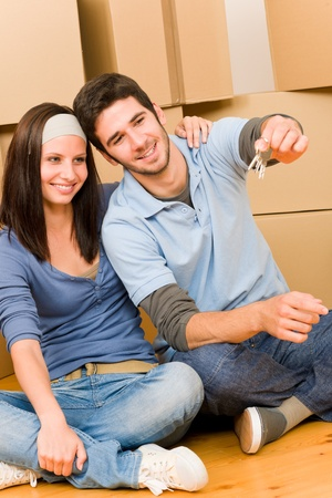 Moving into new home young happy couple holding house keys photo