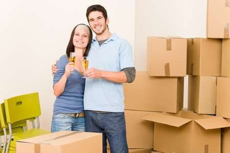 alcohol cardboard: Moving into new home young happy couple celebrating toast Champagne