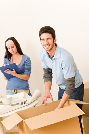 Moving new home young  happy couple unpacking cardboard boxes together Stock Photo