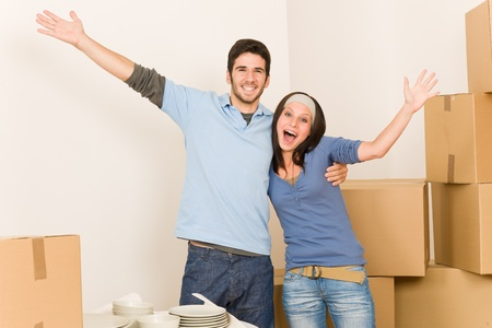 Moving new home young cheerful couple unpacking cardboard boxes together photo