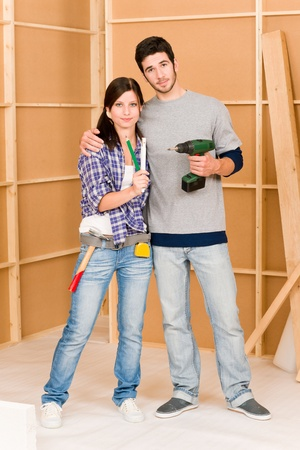 cordless: Home improvement young happy couple with repair tool hand drill ruler Stock Photo