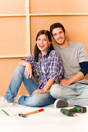 Home improvement young cheerful couple repair tool relax on floor photo