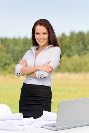 Young architect woman in sunny nature behind table laptop smiling Stock Photo - 10449526