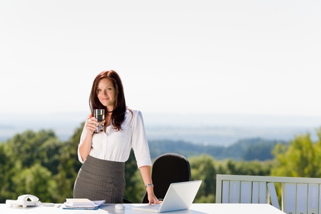 Young businesswoman in sunny nature office with laptop behind table photo