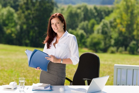 Young businesswoman in sunny nature office holding folders behind table photo