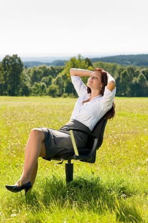 donna seduta sedia: Giovane imprenditrice prato soleggiato rilassarsi sulla poltrona natura attraente Archivio Fotografico