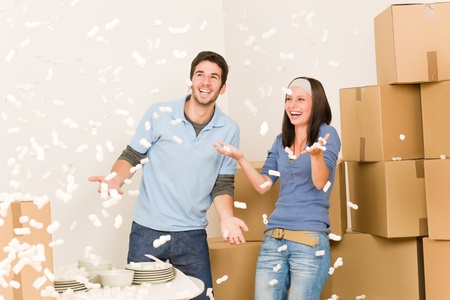 man nuts: Moving home young cheerful couple throw foam peanuts unpacking boxes