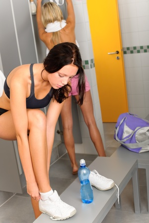 Locker room two sportive women getting ready for fitness training shower photo