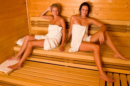 perspiration: Sauna two healthy beautiful women relaxing sitting wrapped in towel