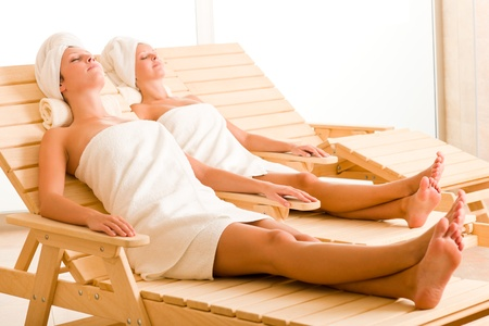 Spa luxury relax room two beautiful women lying on sun-beds photo